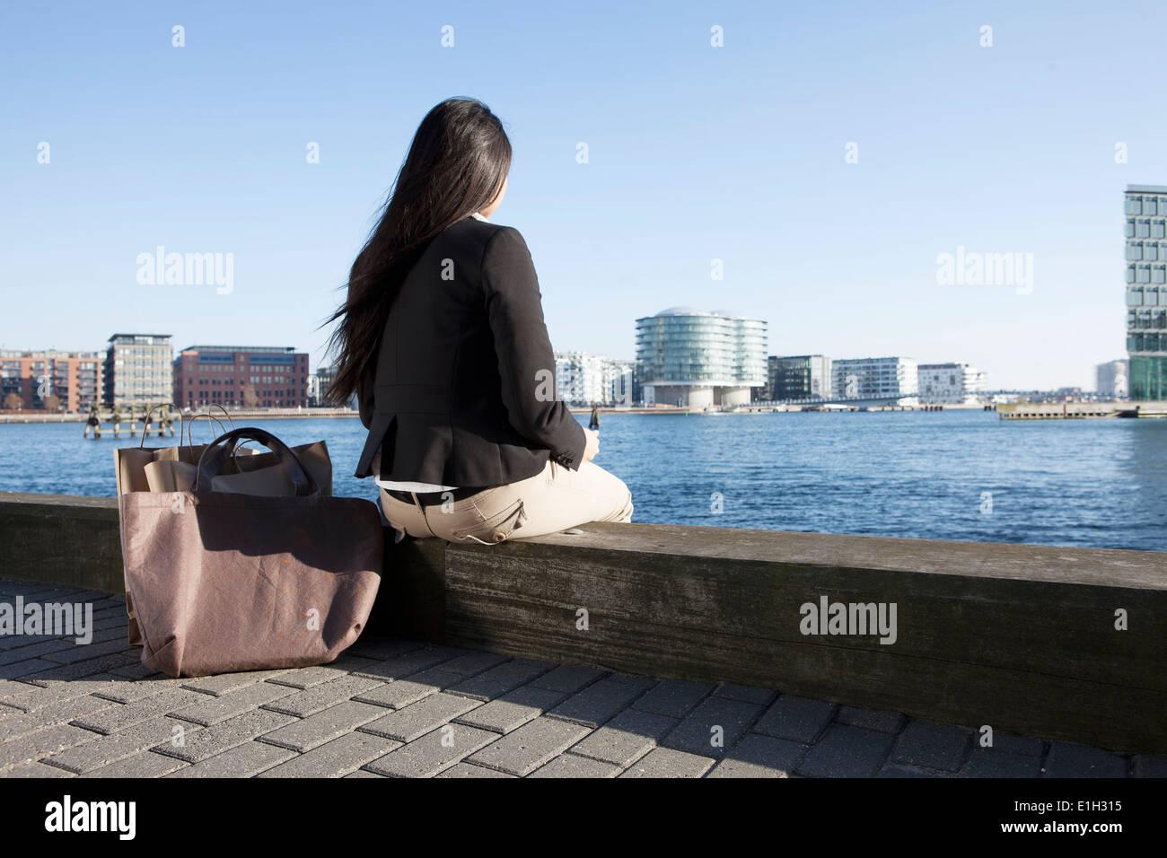 Business woman taking break by waterfront, Copenhagen, Denmark - Stock Image