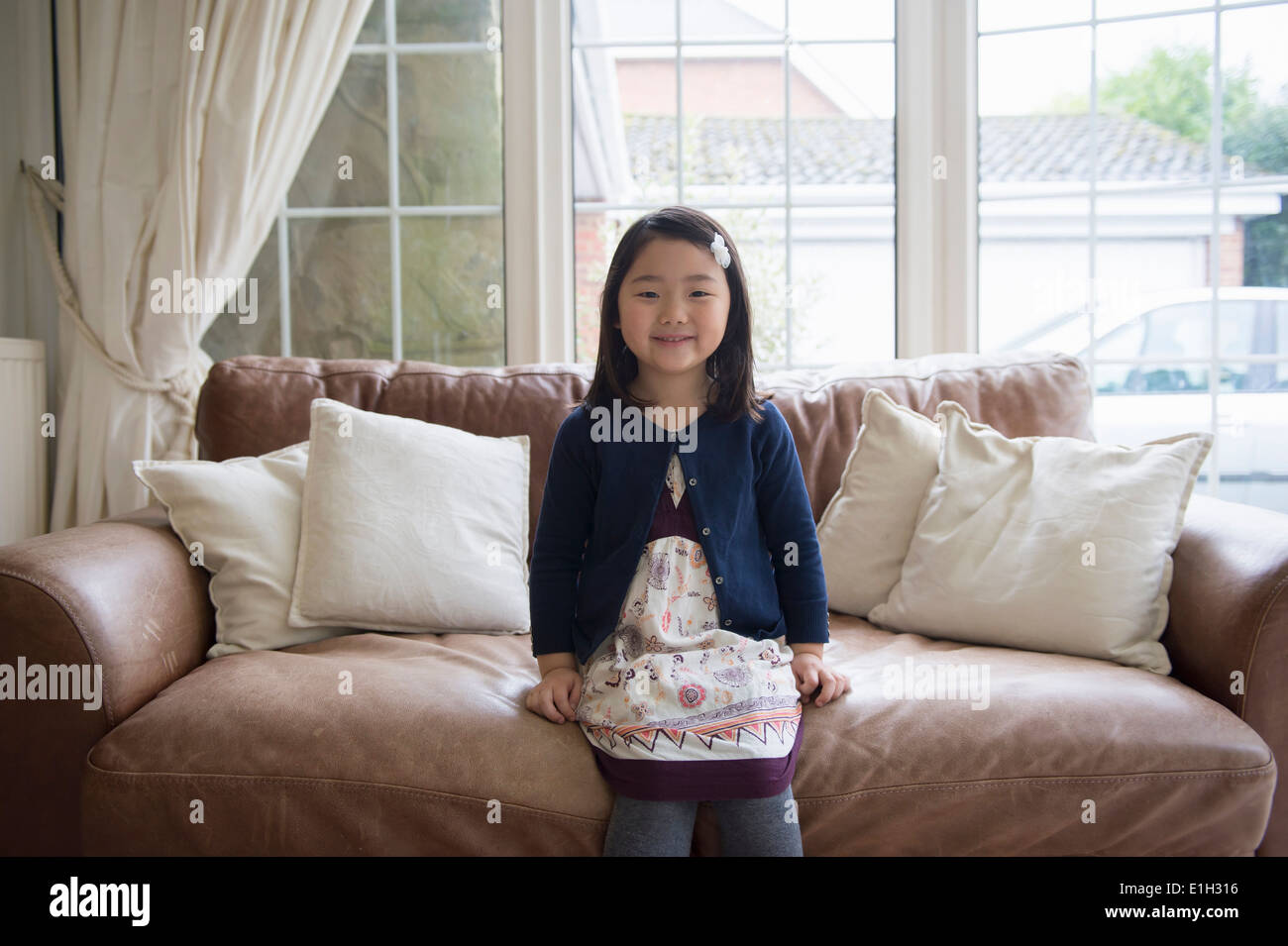 Portrait of young girl sitting on sofa - Stock Image