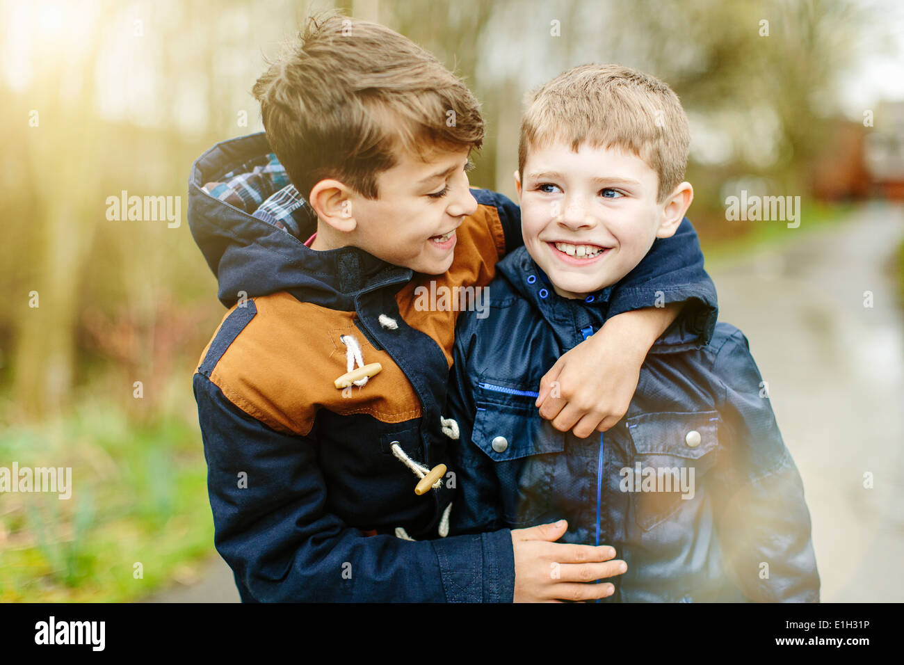 Brothers hugging outdoors - Stock Image