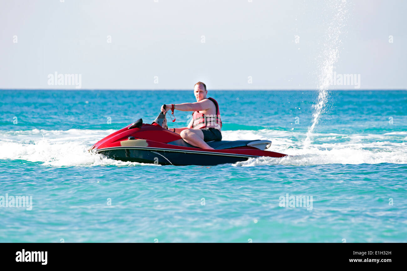 Young guy cruising on the caribbic sea on a jet ski - Stock Image