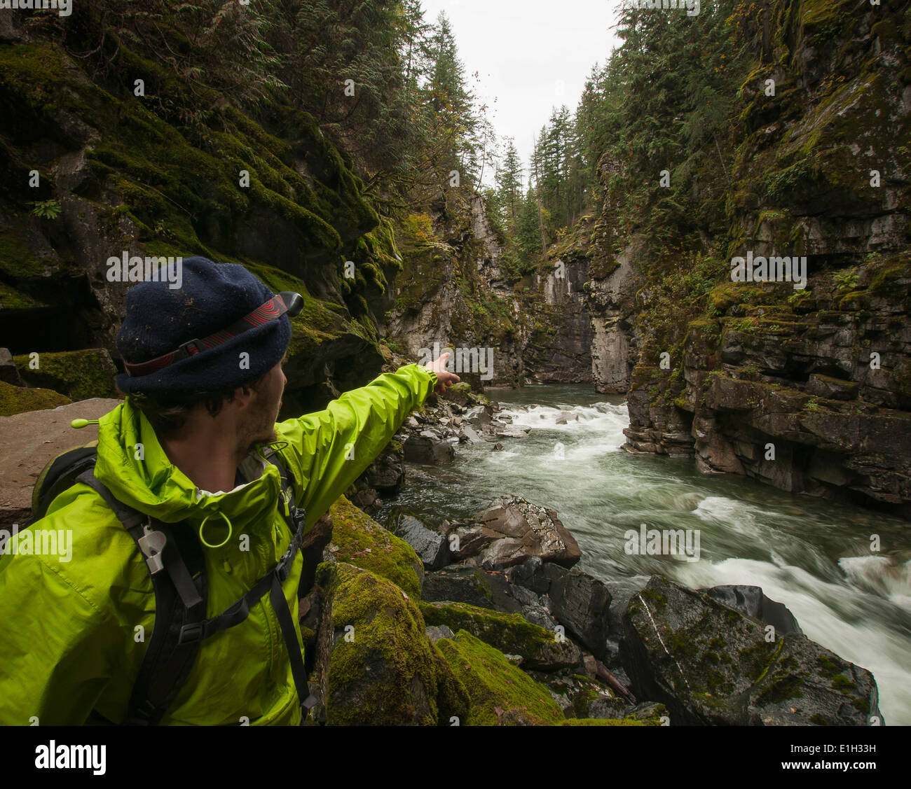 Hiker points cliffs, Coquihalla Canyon provincial Park and Othello Tunnels, Trans-Canada Trail, Hope, British Columbia, Canada - Stock Image