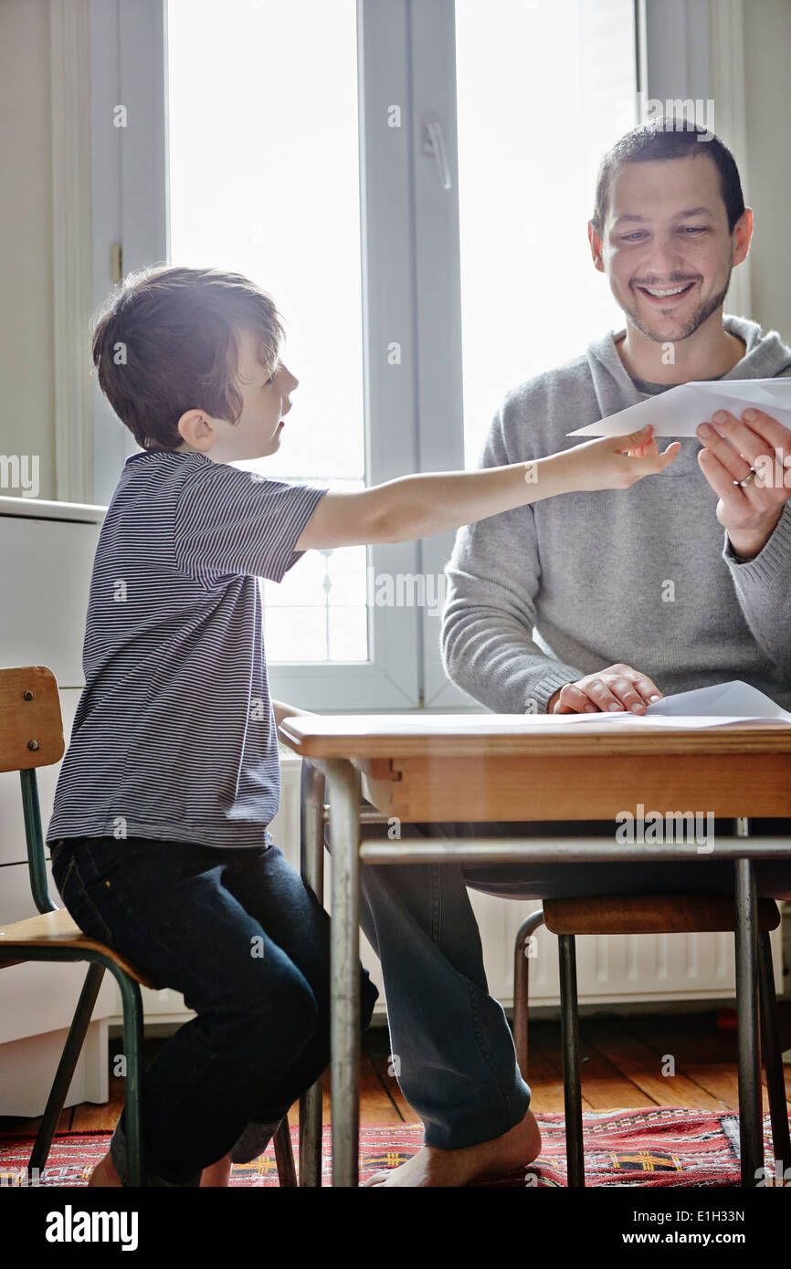 Father holding paper plane for son - Stock Image