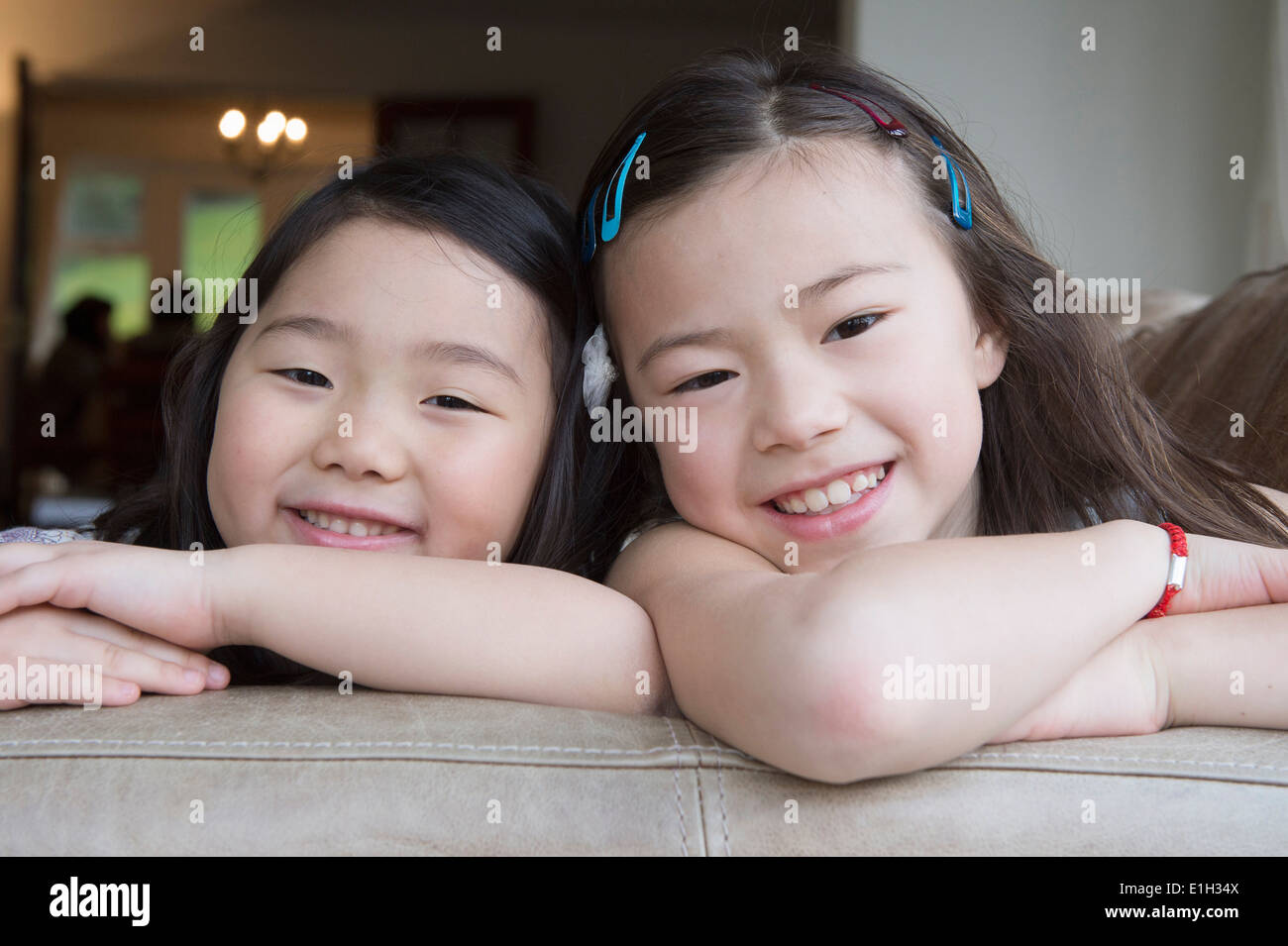 Portrait of two young girls leaning on sofa - Stock Image