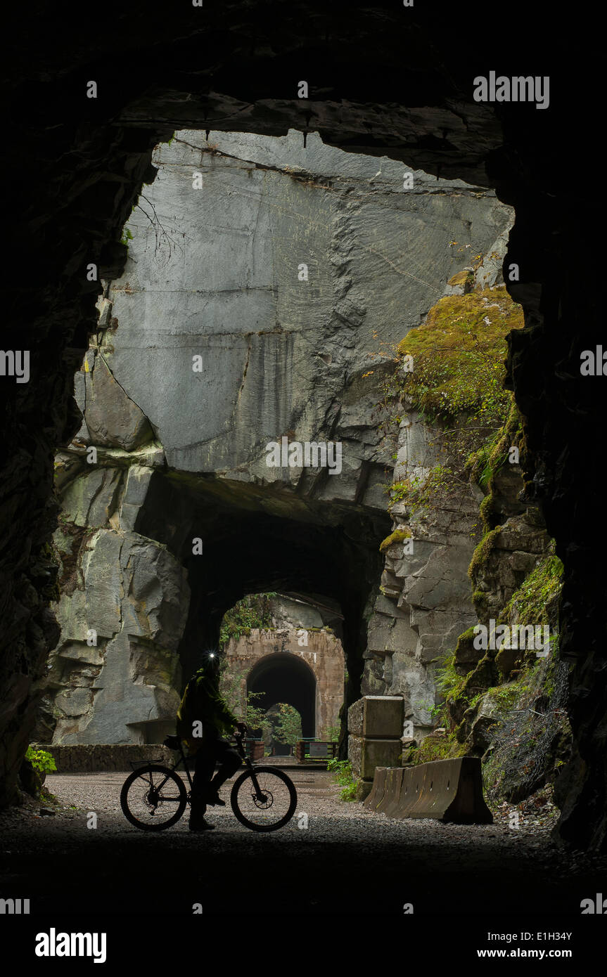 Cyclist inside one of Othello Tunnels, Coquihalla Provincial Park, KVR Trail, Trans-Canada Trail, British Columbia, - Stock Image