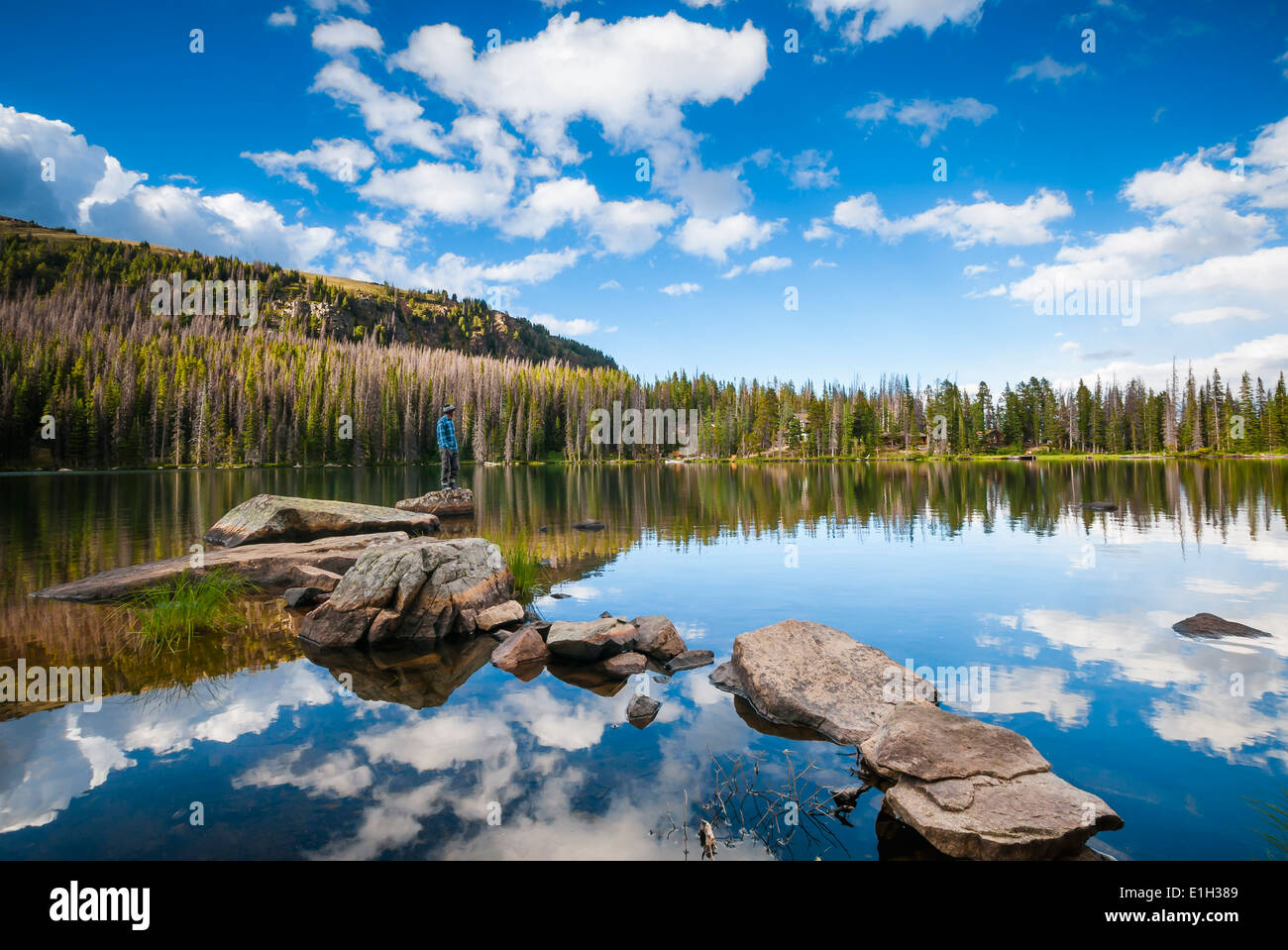 Hiker on pathway of rocks with reflections of clouds, Quinescoe Lake Cathedral Lakes Provincial Park British Columbia Canada - Stock Image
