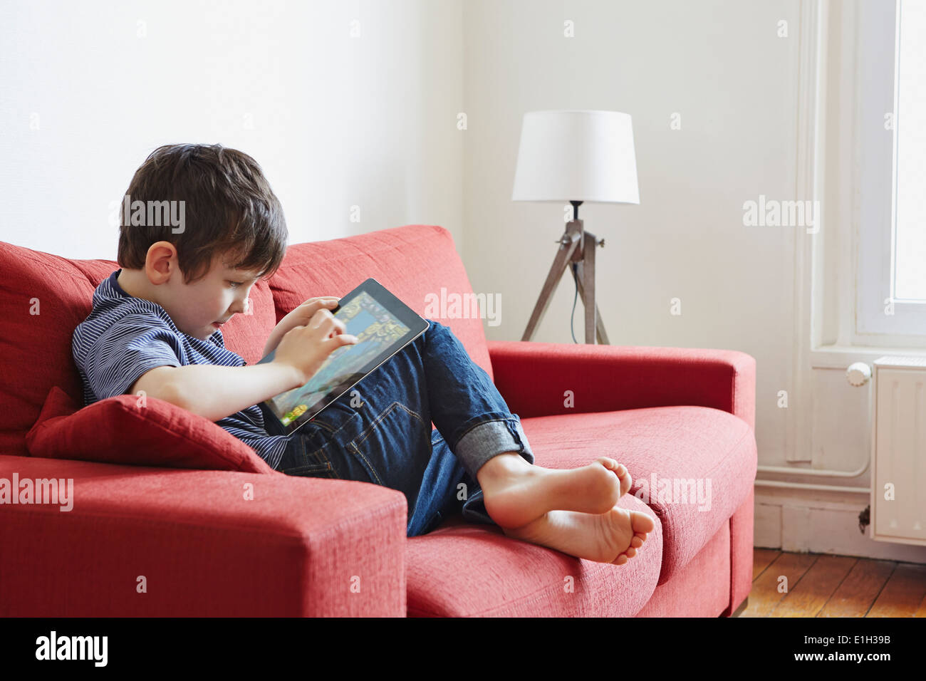 Boy using digital tablet - Stock Image