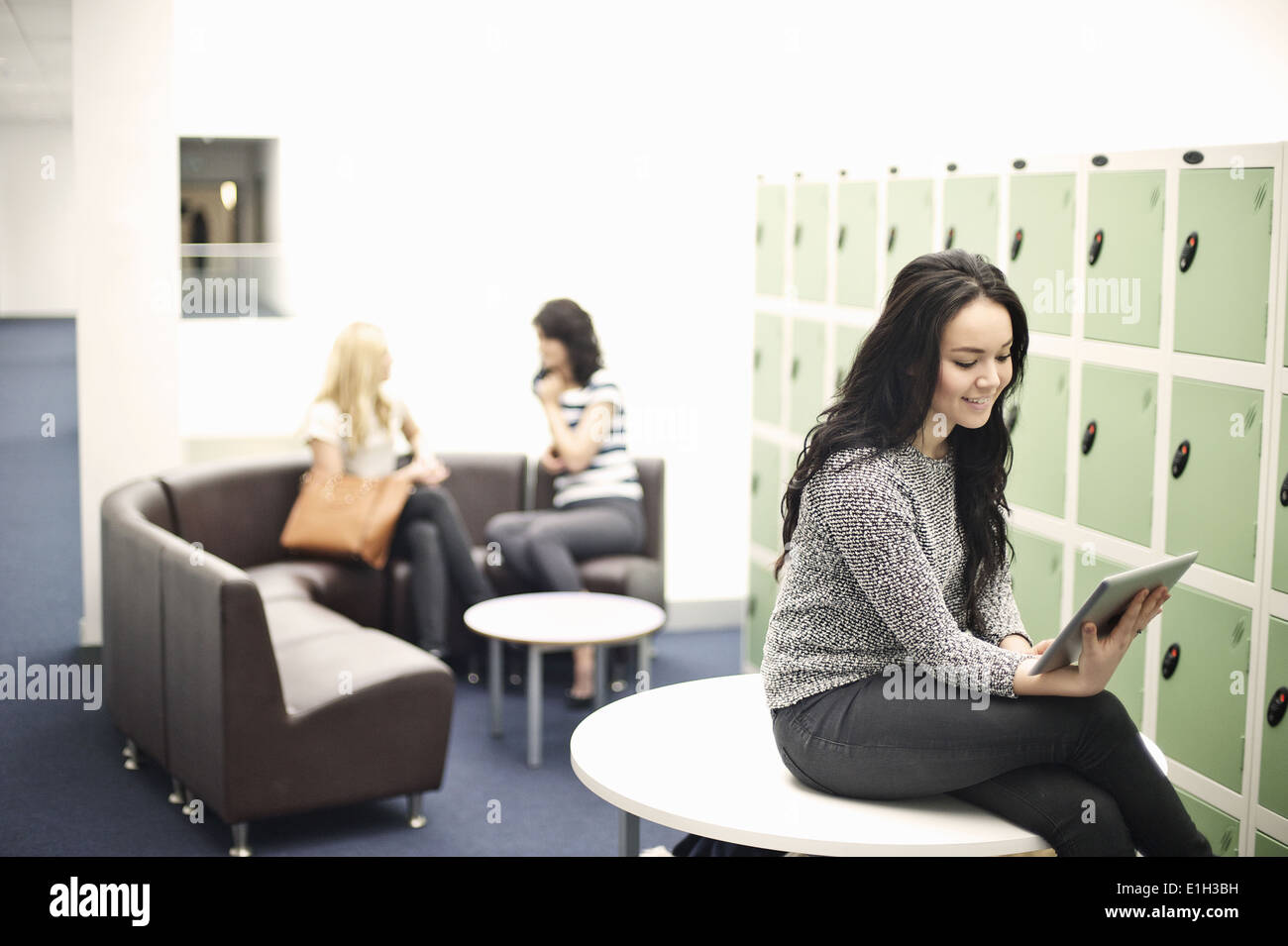 Young woman sitting on table using digital tablet - Stock Image