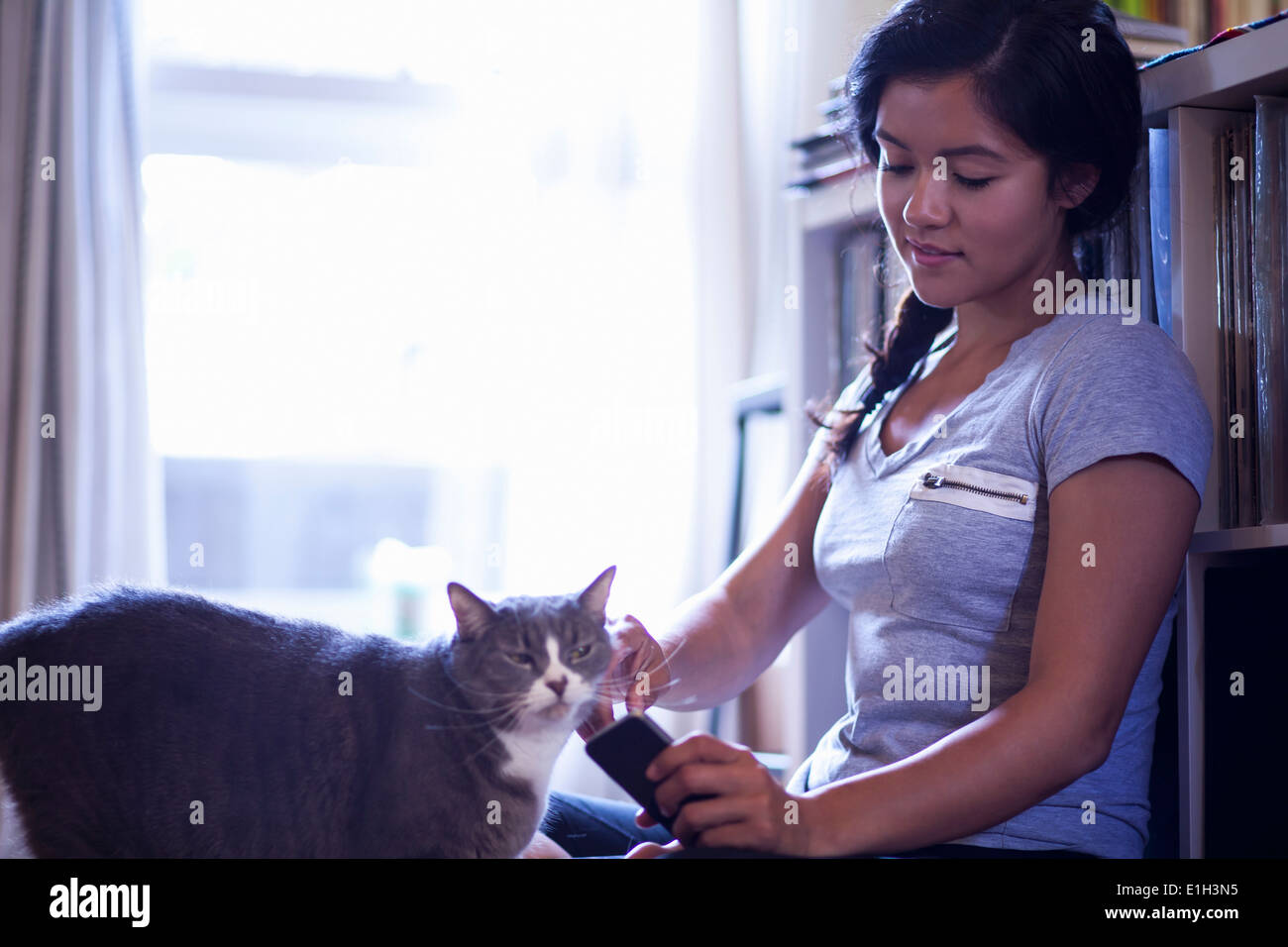 Young woman holding cellular phone stroking cat - Stock Image