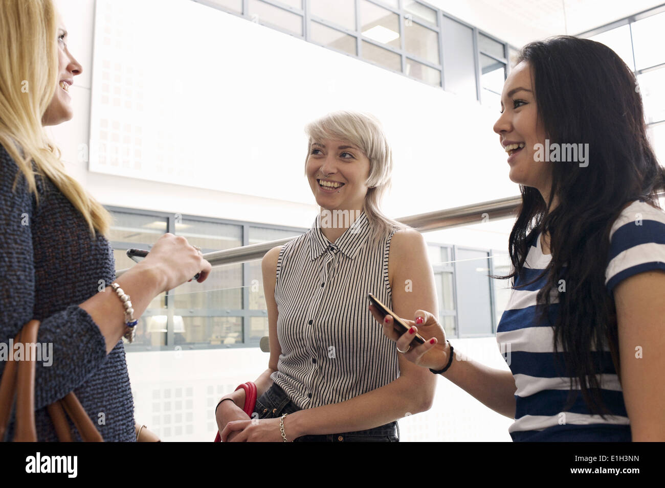 Young women using cell phones - Stock Image