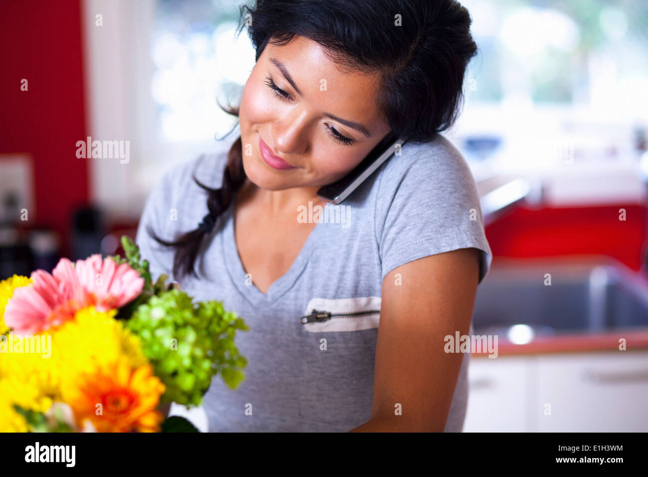 Young woman using cellular phone in kitchen - Stock Image
