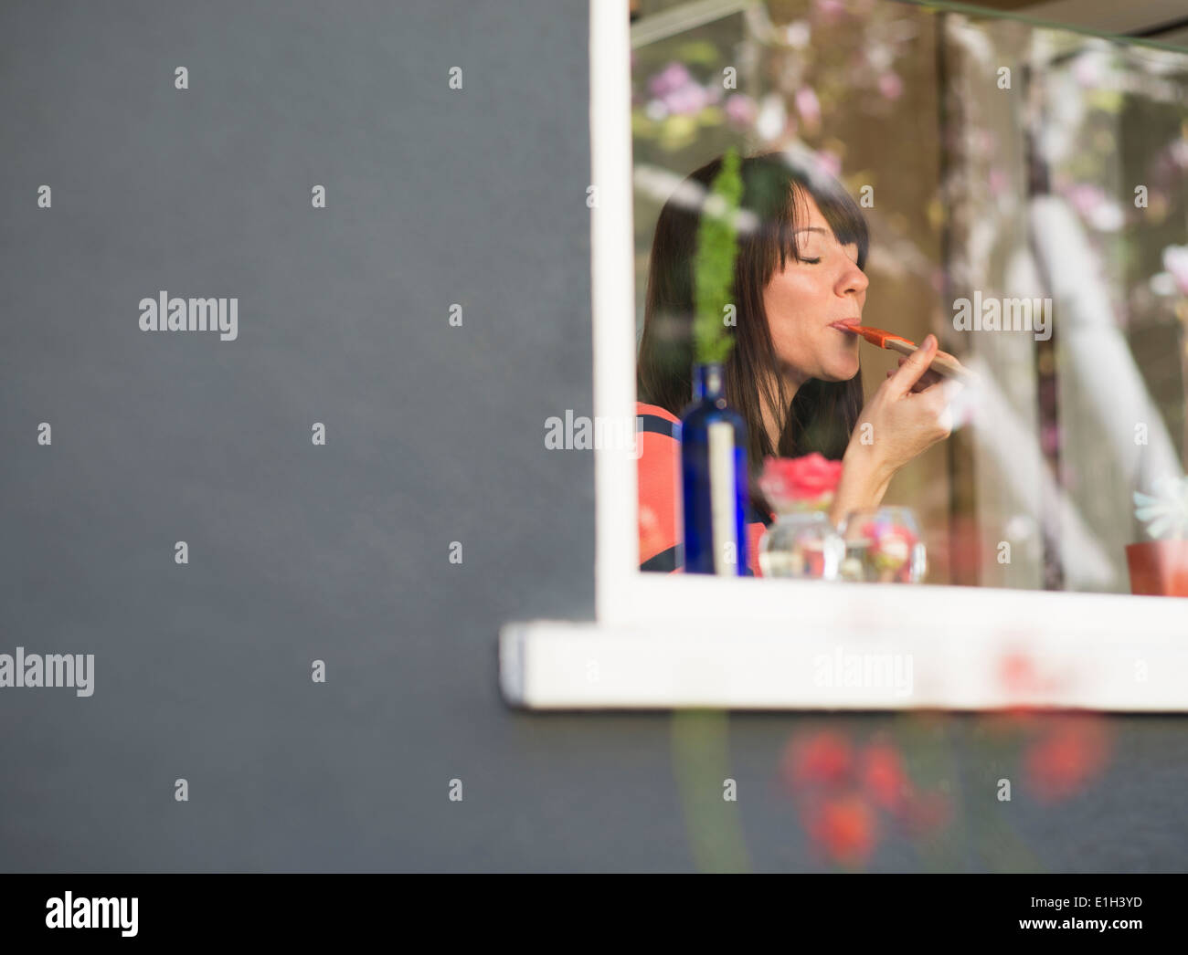 Mature woman at house window tasting food from spatula - Stock Image