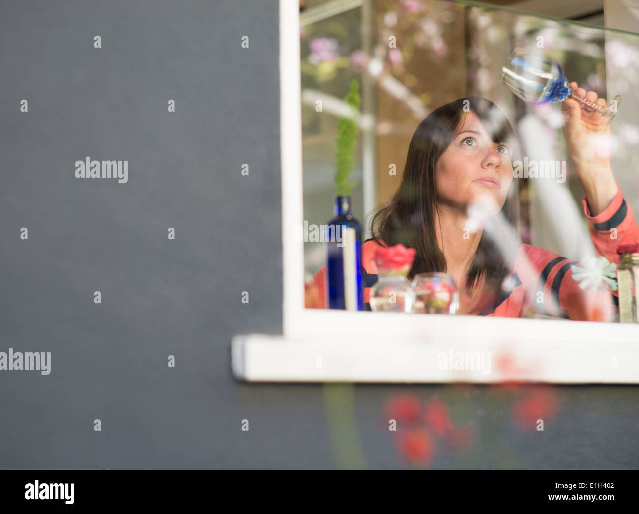 Mature woman at house window examining wine glass - Stock Image