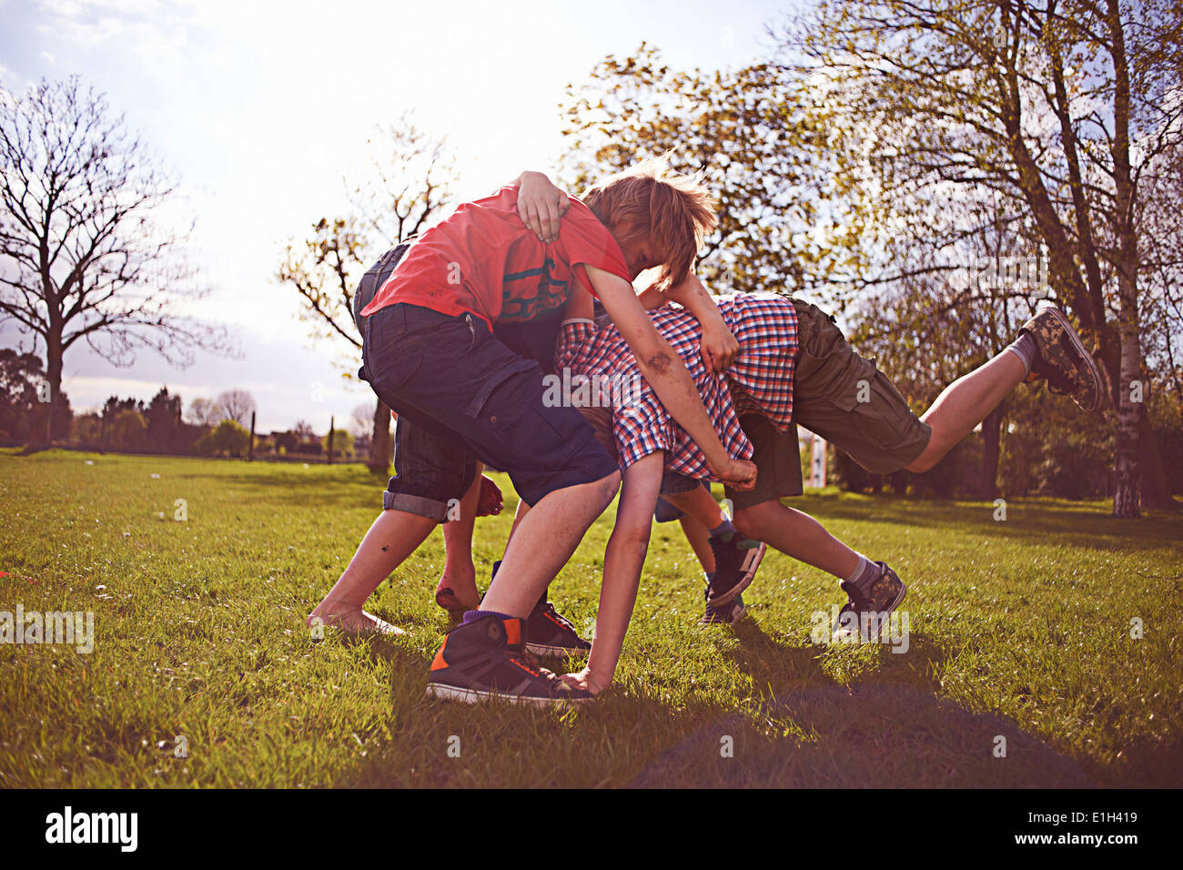 Boys play fighting on playing field Stock Photo