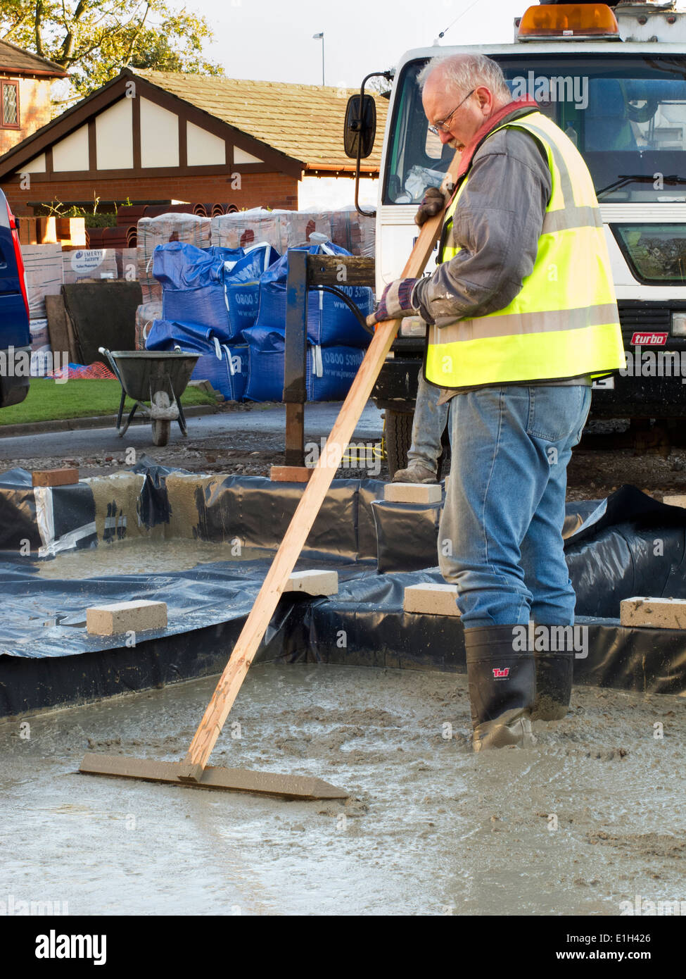self building house, pouring floor slab, man roughly levelling concrete manually Stock Photo