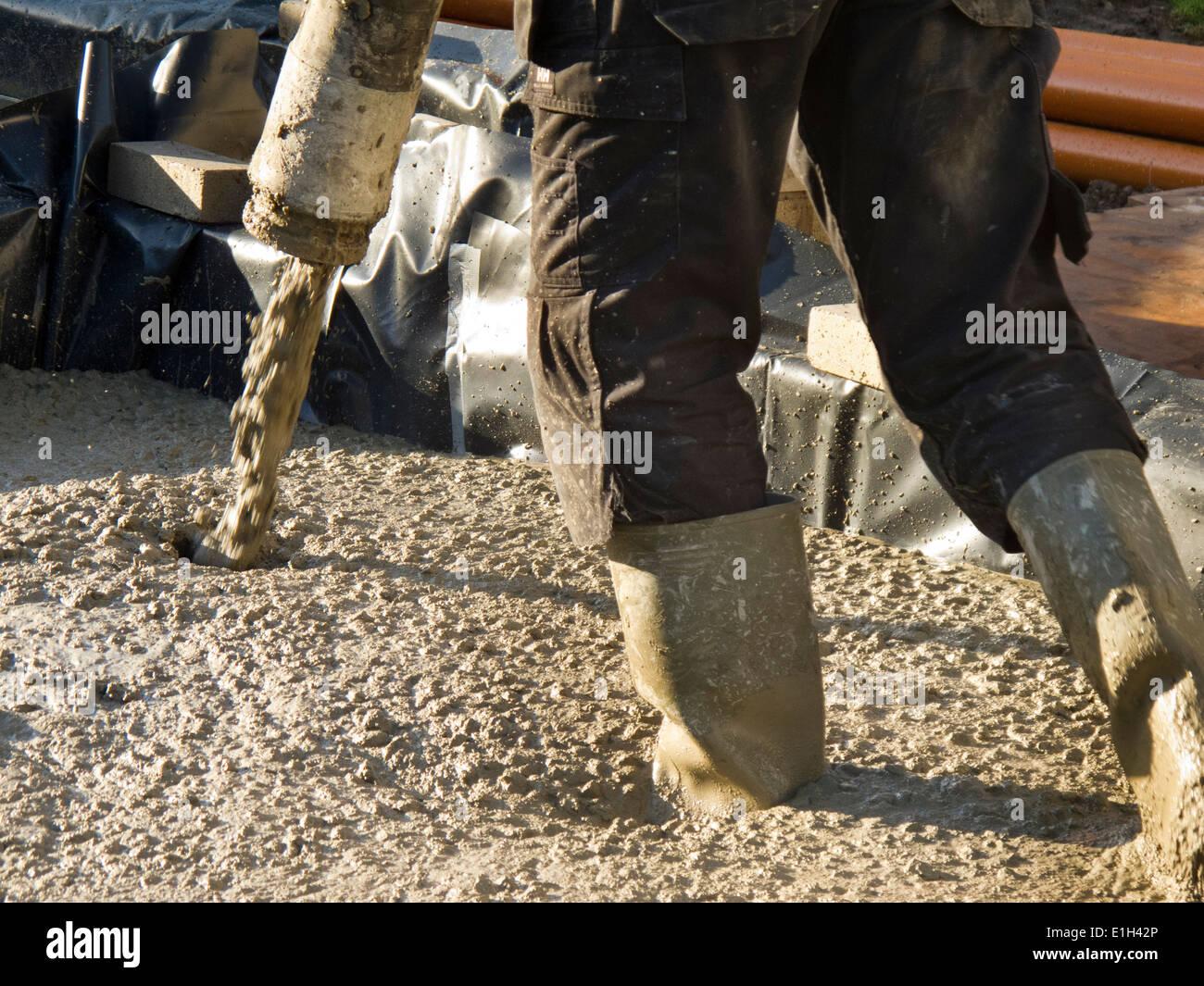 Al932 self building house, man pouring floor slab, directing concrete pump Stock Photo