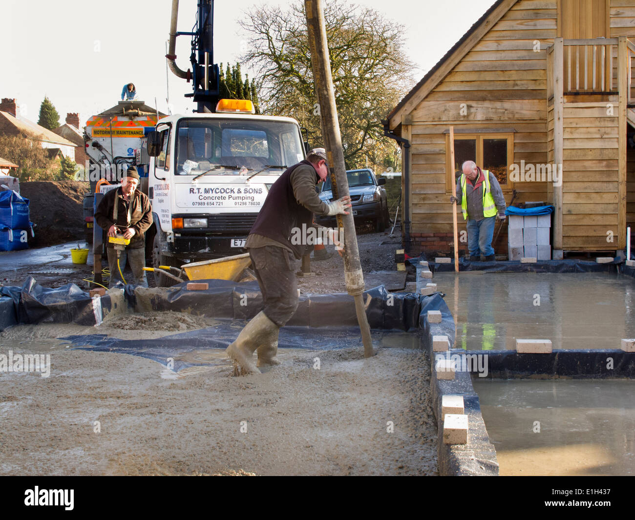 self building house, man pouring floor slab, directing concrete pump Stock Photo