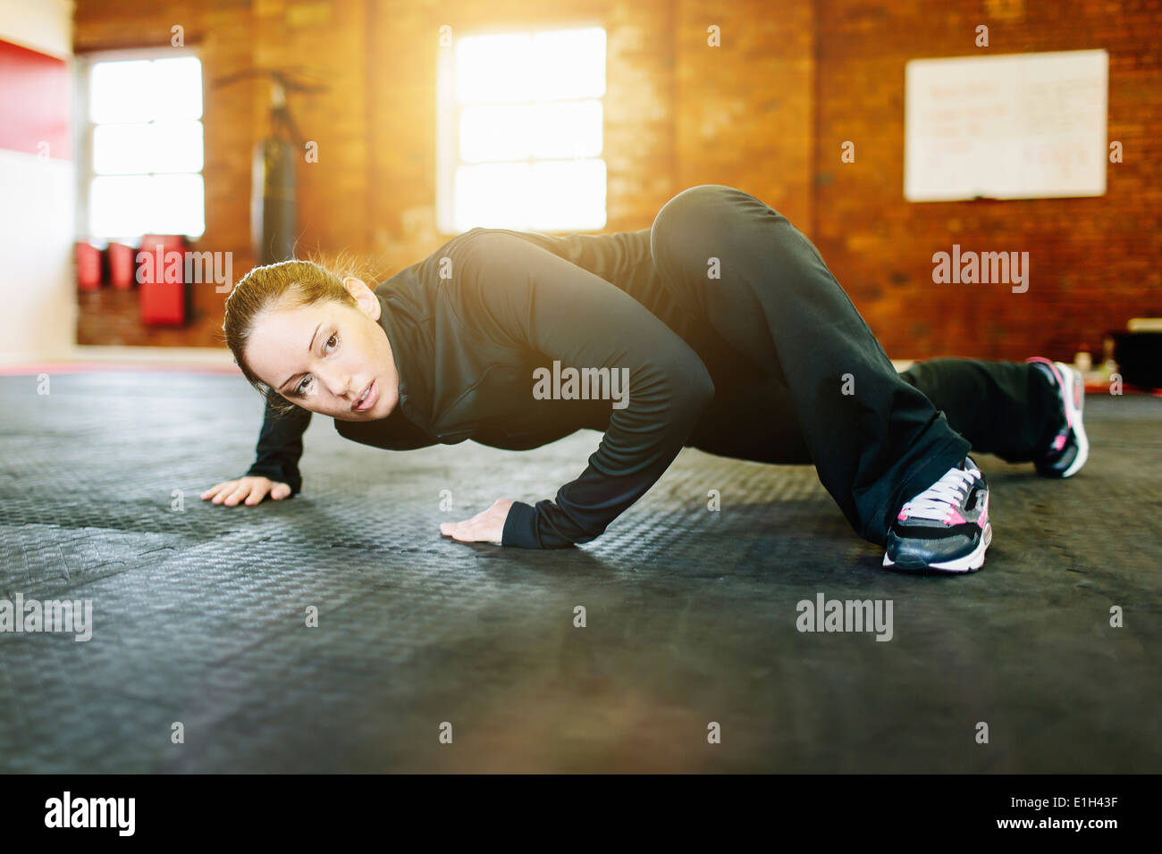 Woman doing stretching exercise in gym - Stock Image
