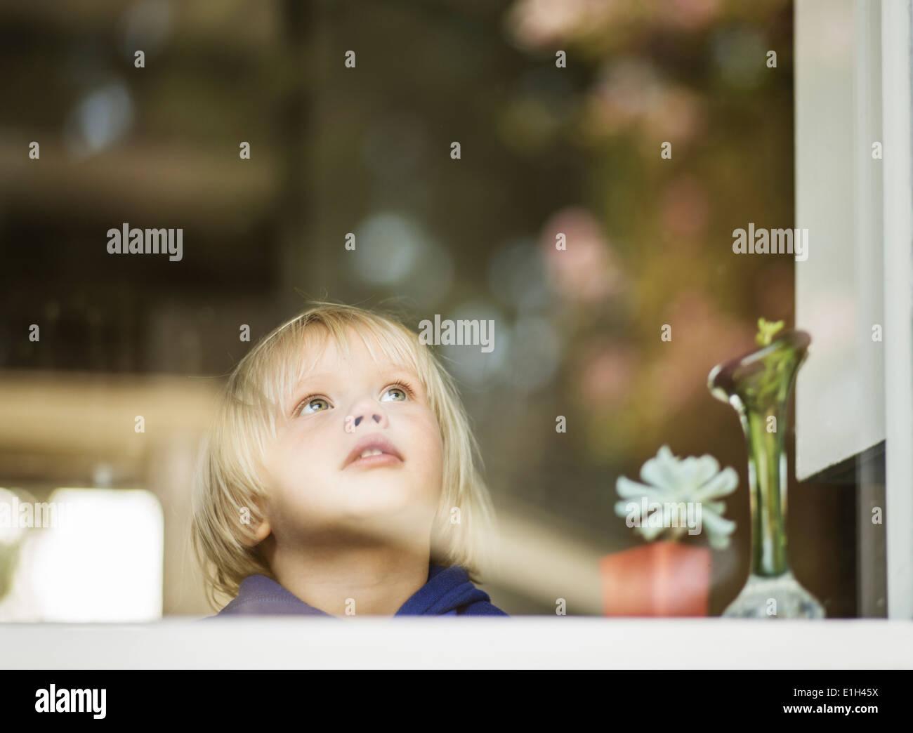Young boy at house window gazing upward - Stock Image