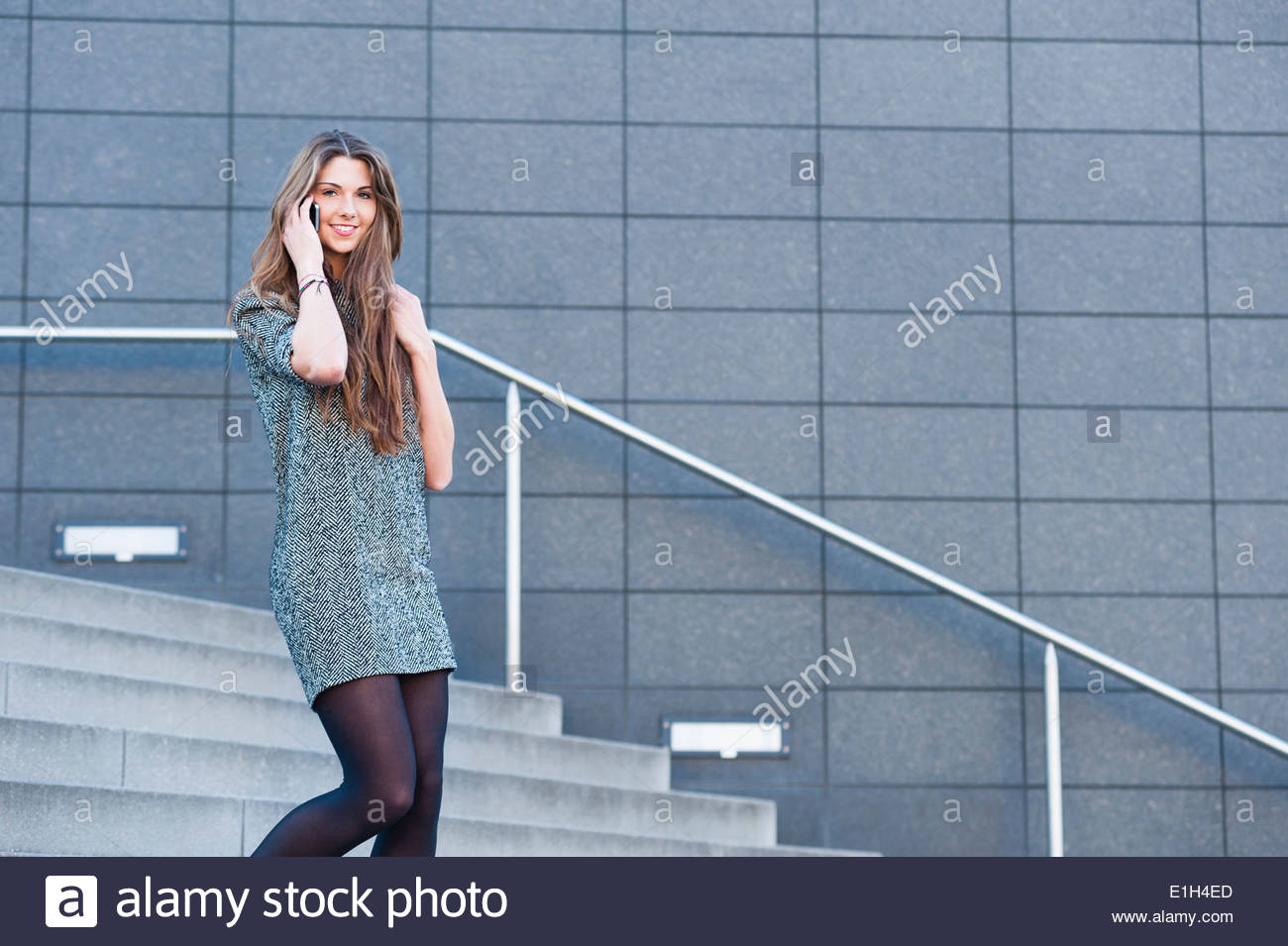 Young woman walking down steps, on phonecall - Stock Image