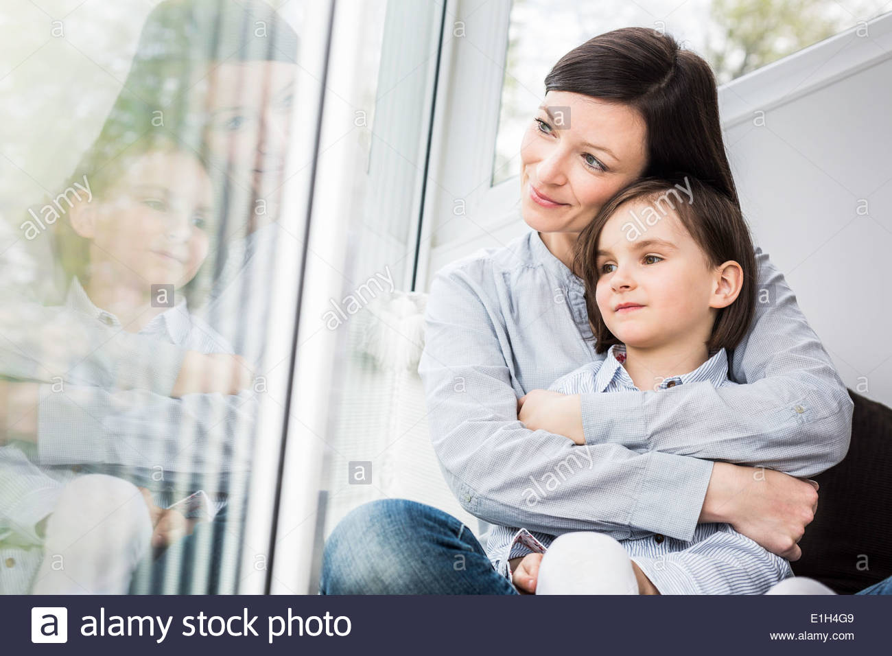 Mother and daughter hugging by window - Stock Image
