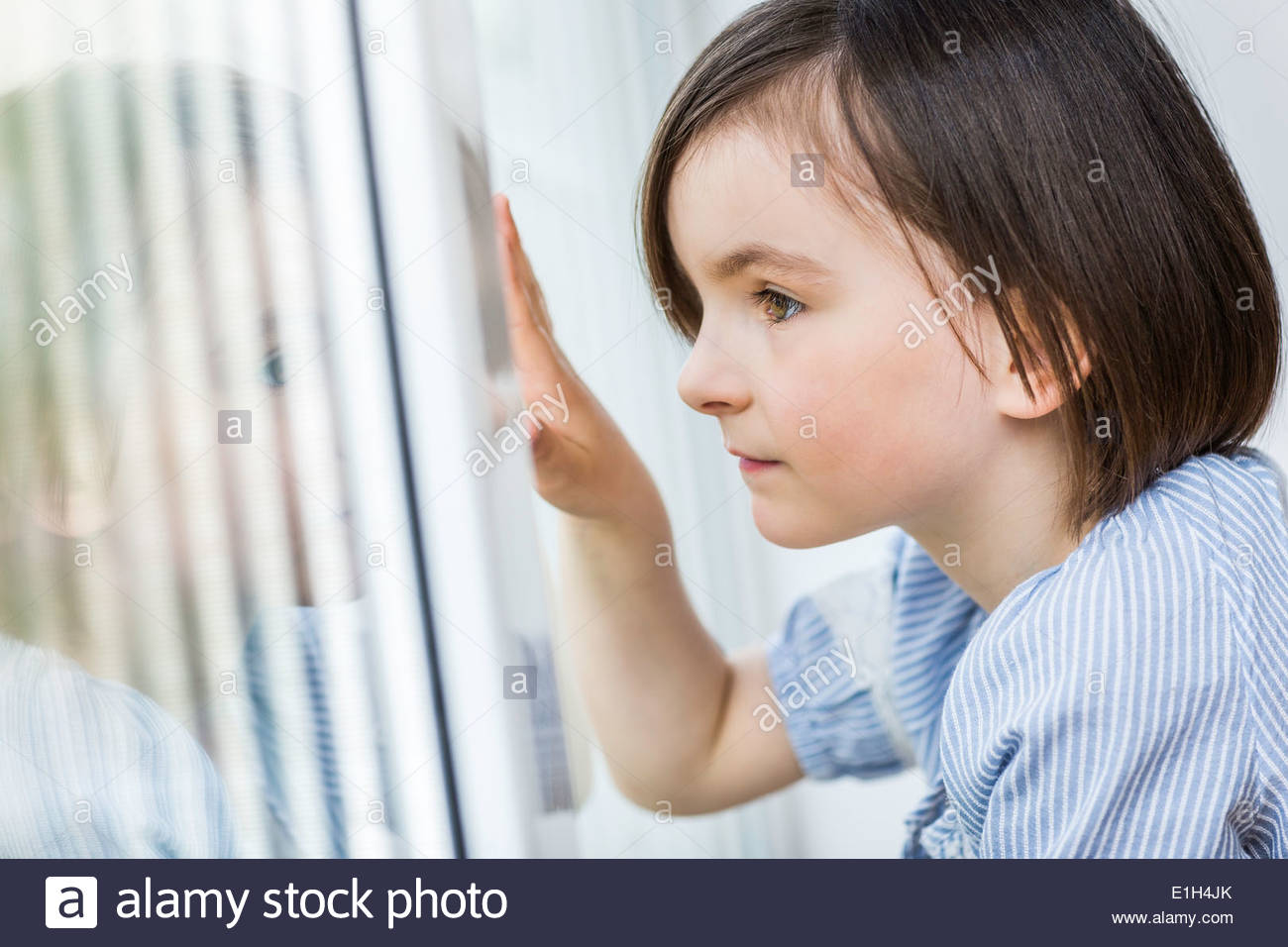 Young girl looking out of window - Stock Image