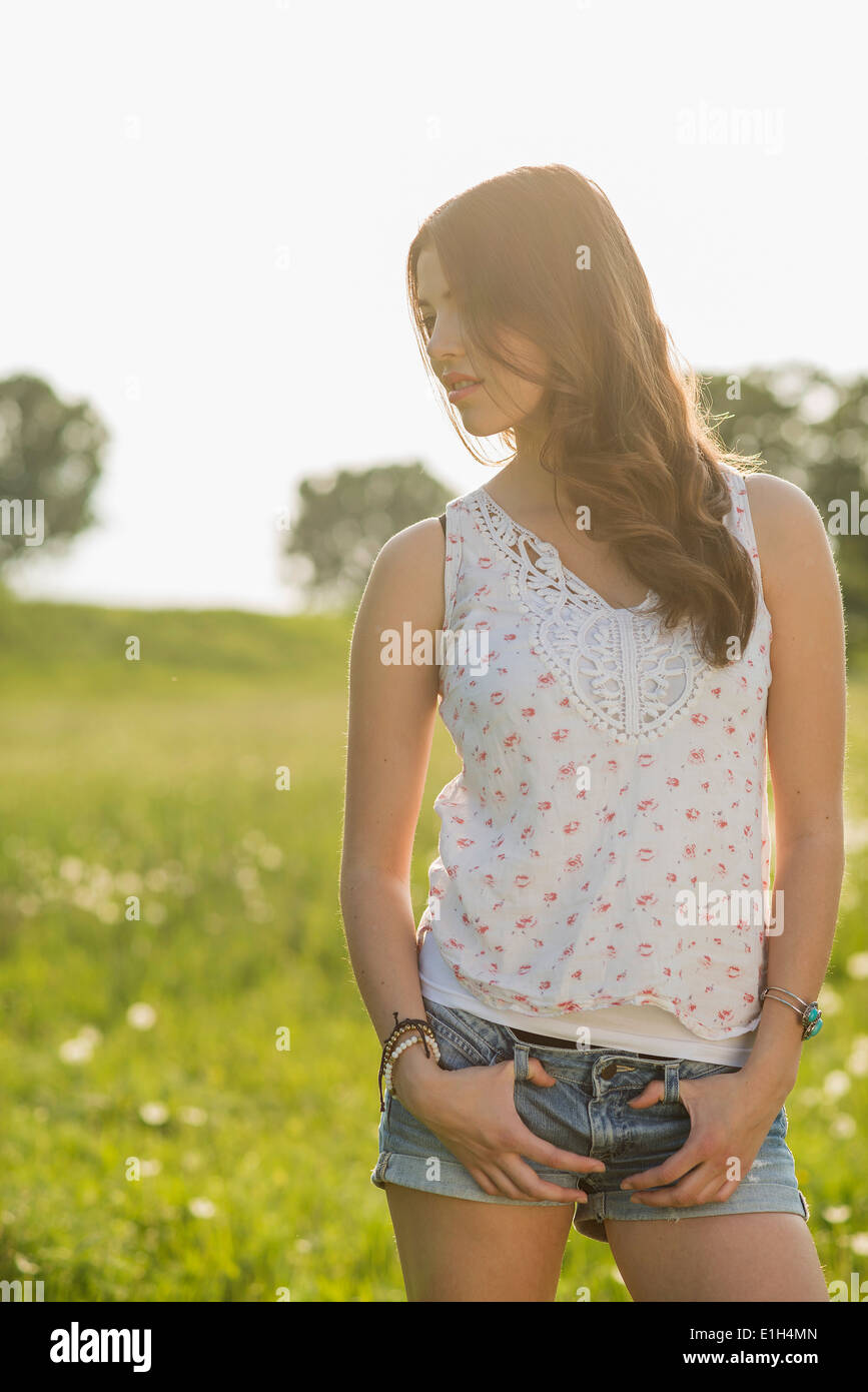 Young woman wearing shorts and vest, portrait - Stock Image