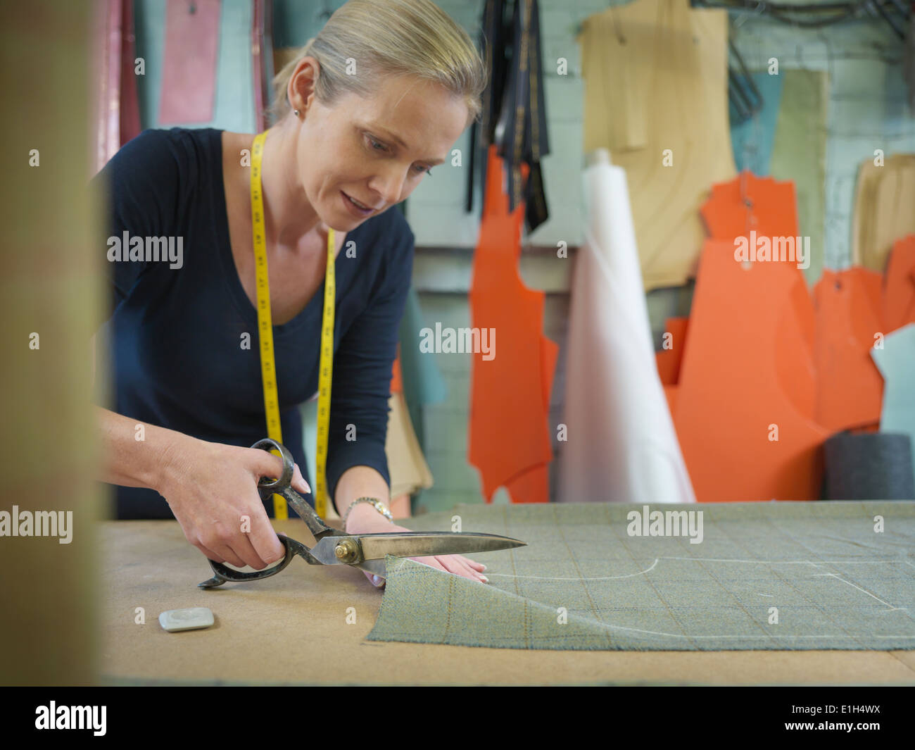 Female worker cutting cloth in garment factory - Stock Image