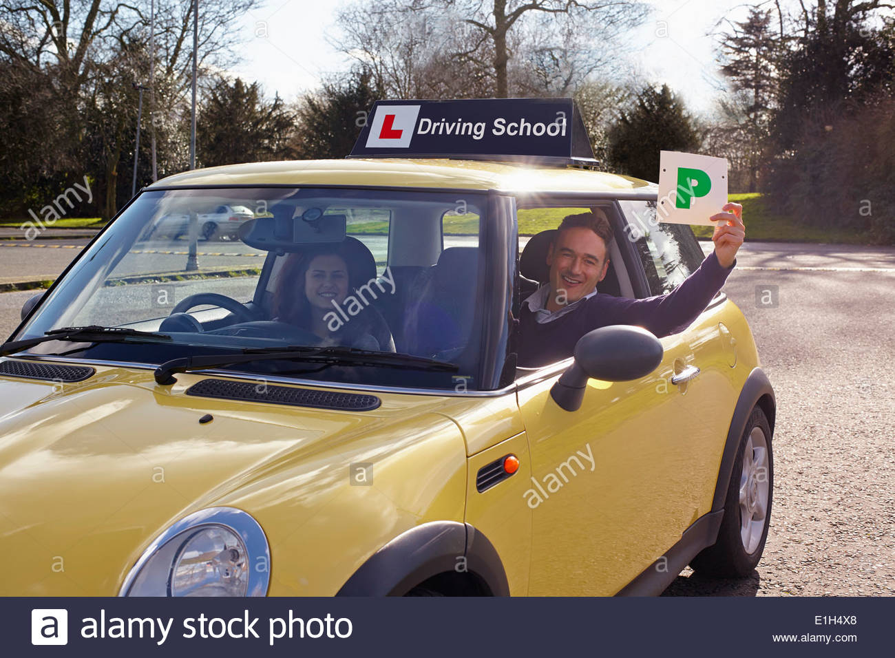 Driving instructor holding Passed Plate out of car window - Stock Image