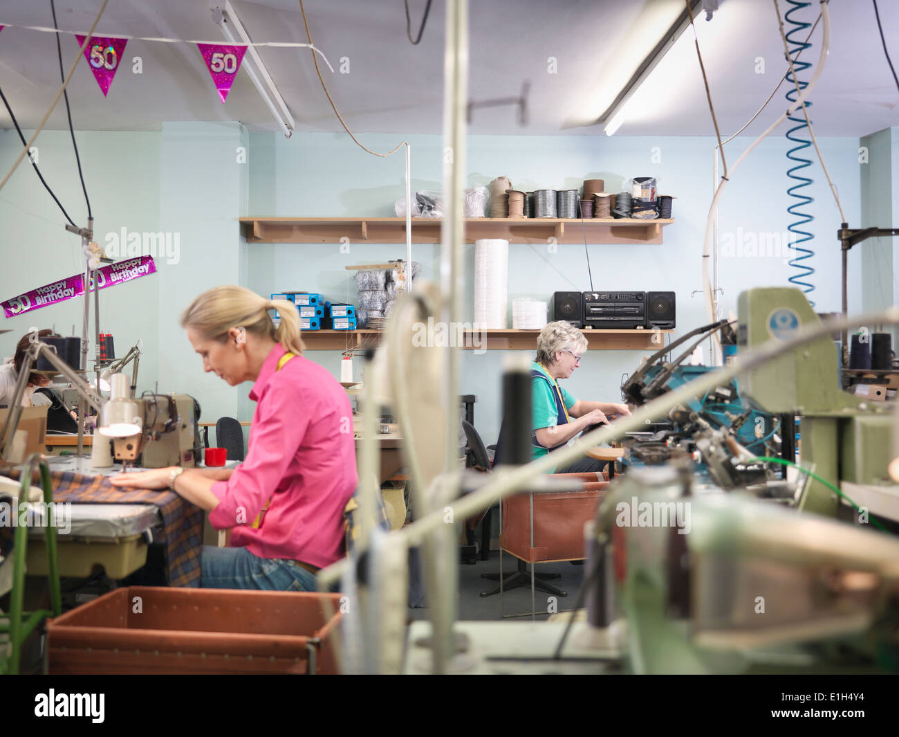 Workers sewing in clothing factory - Stock Image