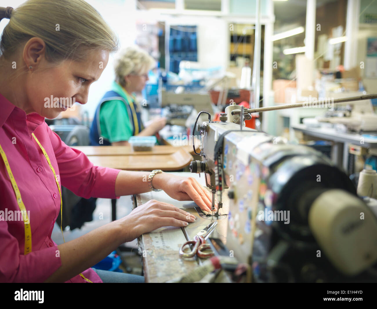 Worker sewing in clothing factory - Stock Image