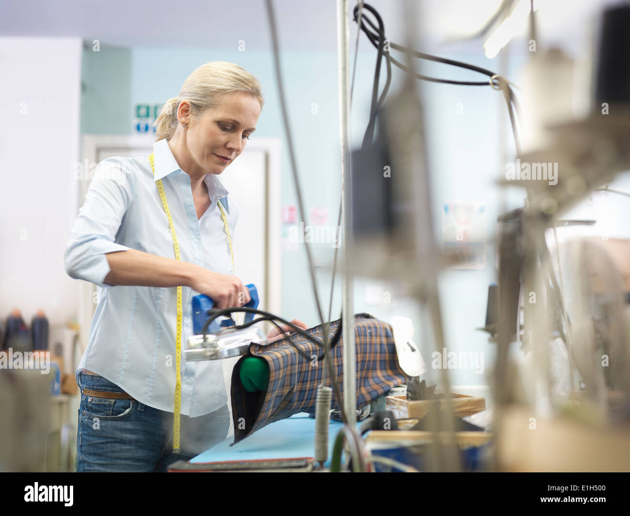 Worker ironing garment in clothing factory - Stock Image