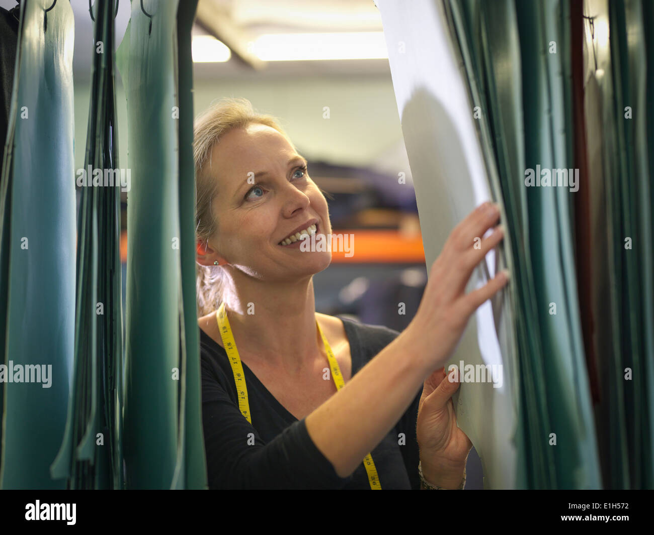 Female worker inspecting patterns in clothing factory Stock Photo