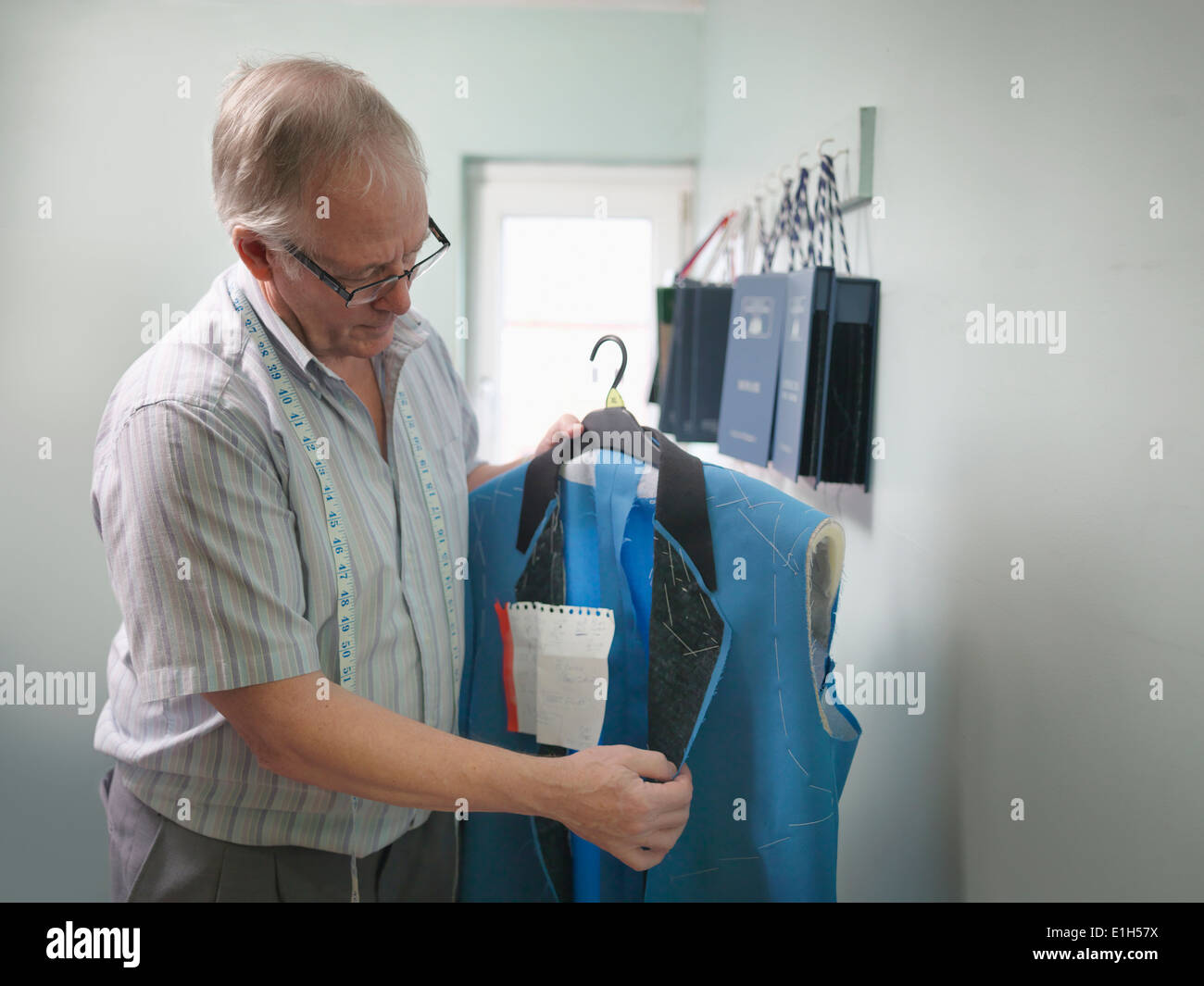 Tailor inspecting clothing in tailoring factory - Stock Image