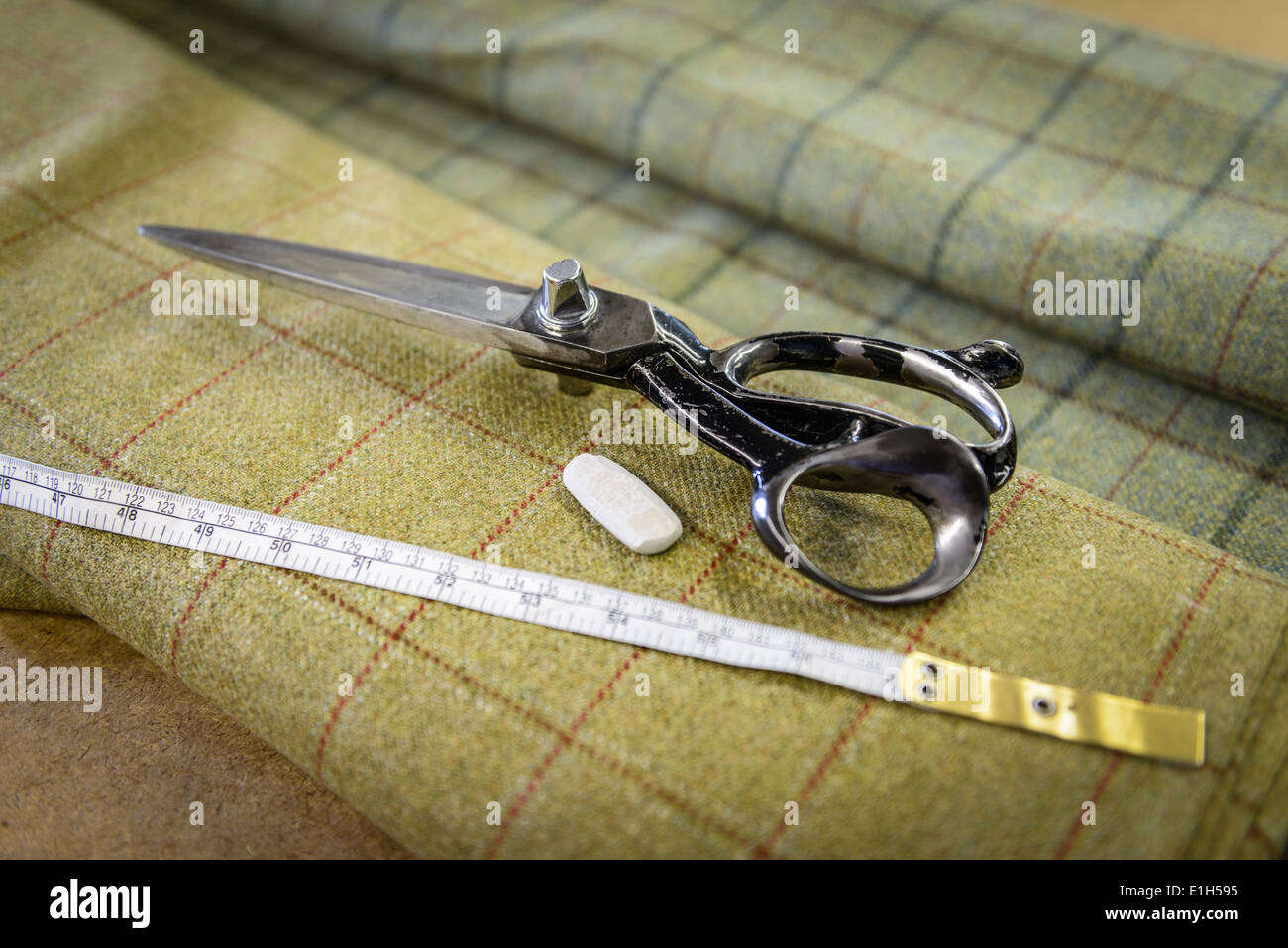 Harris tweed material and scissors in clothing factory - Stock Image