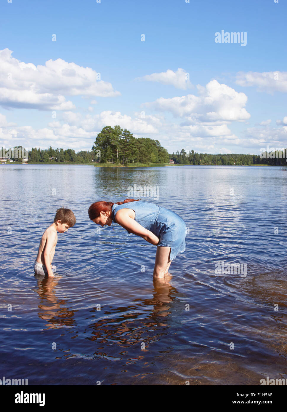 Mother and young son in searching in lake, Gavle, Sweden - Stock Image
