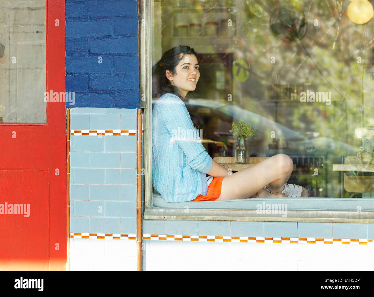 Young woman looking out of cafe window - Stock Image