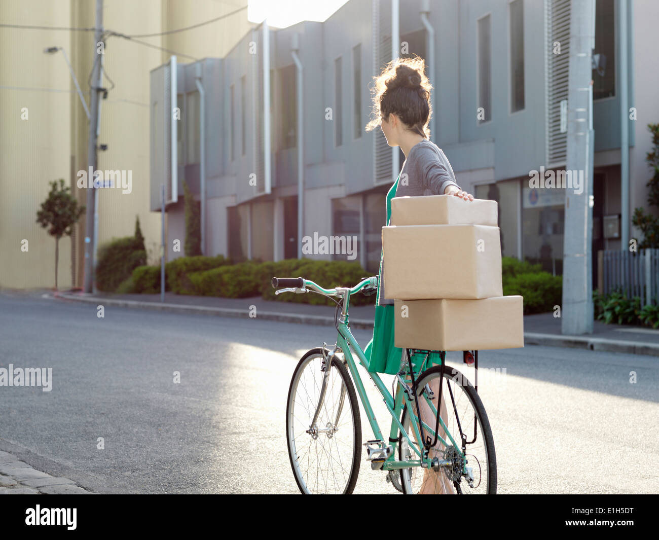 Young woman pushing bicycle with cardboard boxes - Stock Image