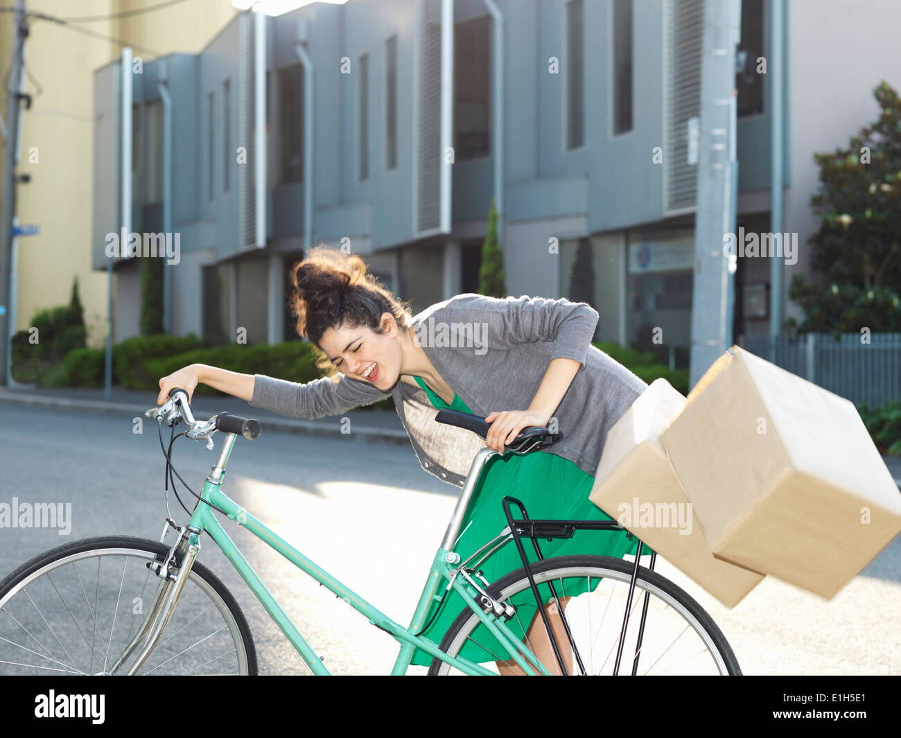 Young woman with bicycle and falling cardboard boxes - Stock Image