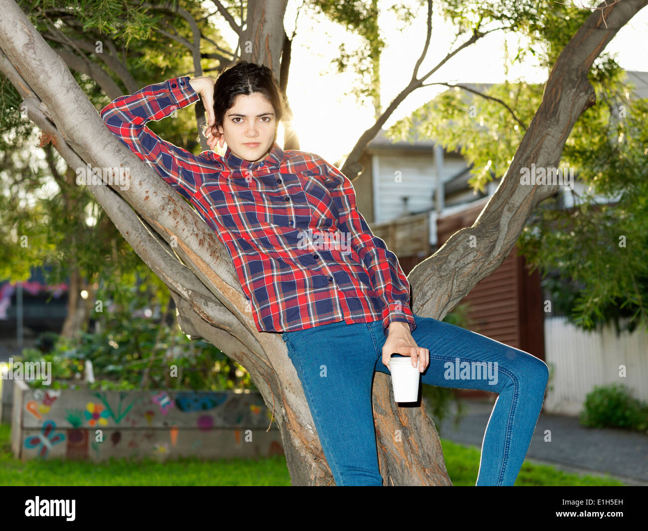 Portrait of confident young woman reclining against tree - Stock Image