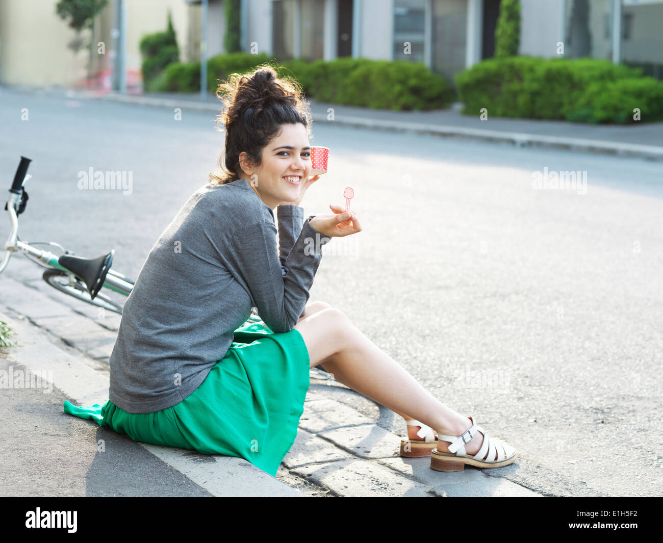 Portrait of young woman eating ice cream on sidewalk - Stock Image