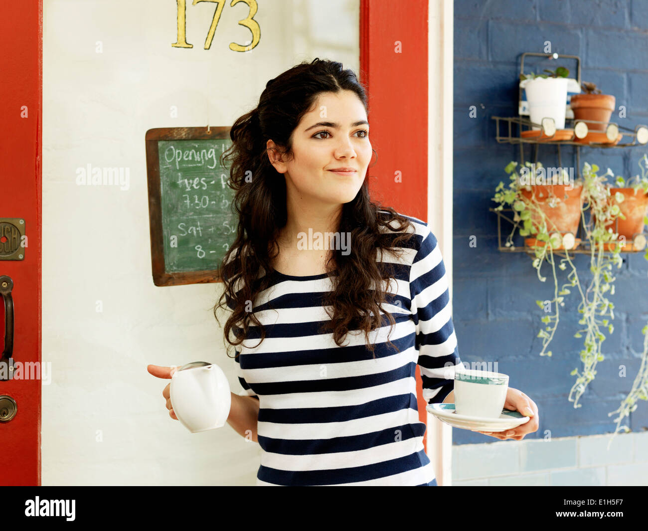 Young female waitress serving coffee outdoors - Stock Image