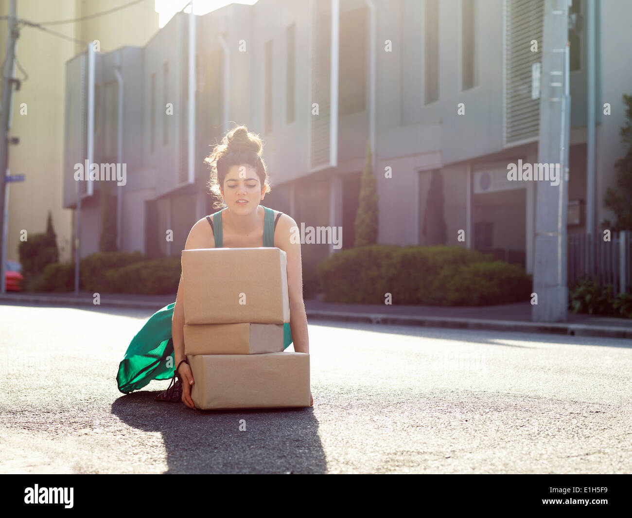 Young woman crouching to lift stack of cardboard boxes - Stock Image