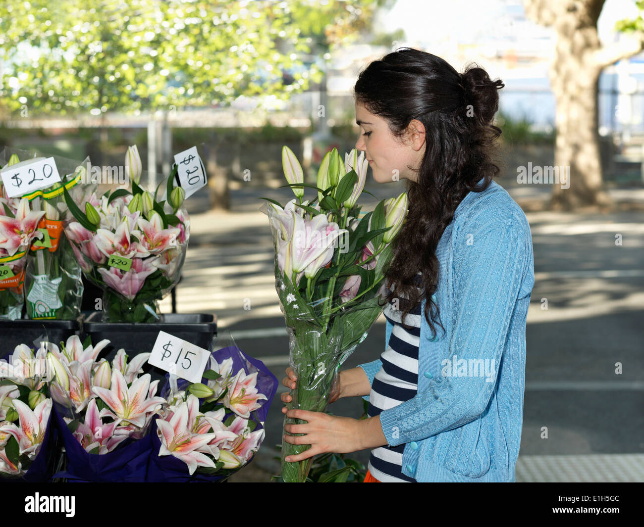 Young woman smelling cut flowers on street - Stock Image