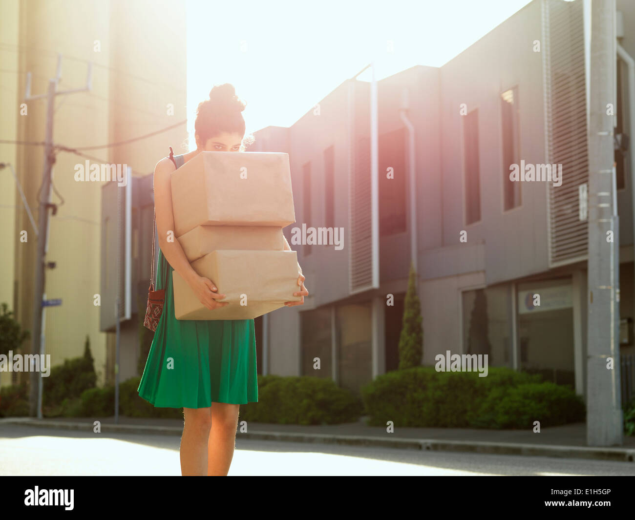 Young woman carrying and peeking over stack of boxes - Stock Image