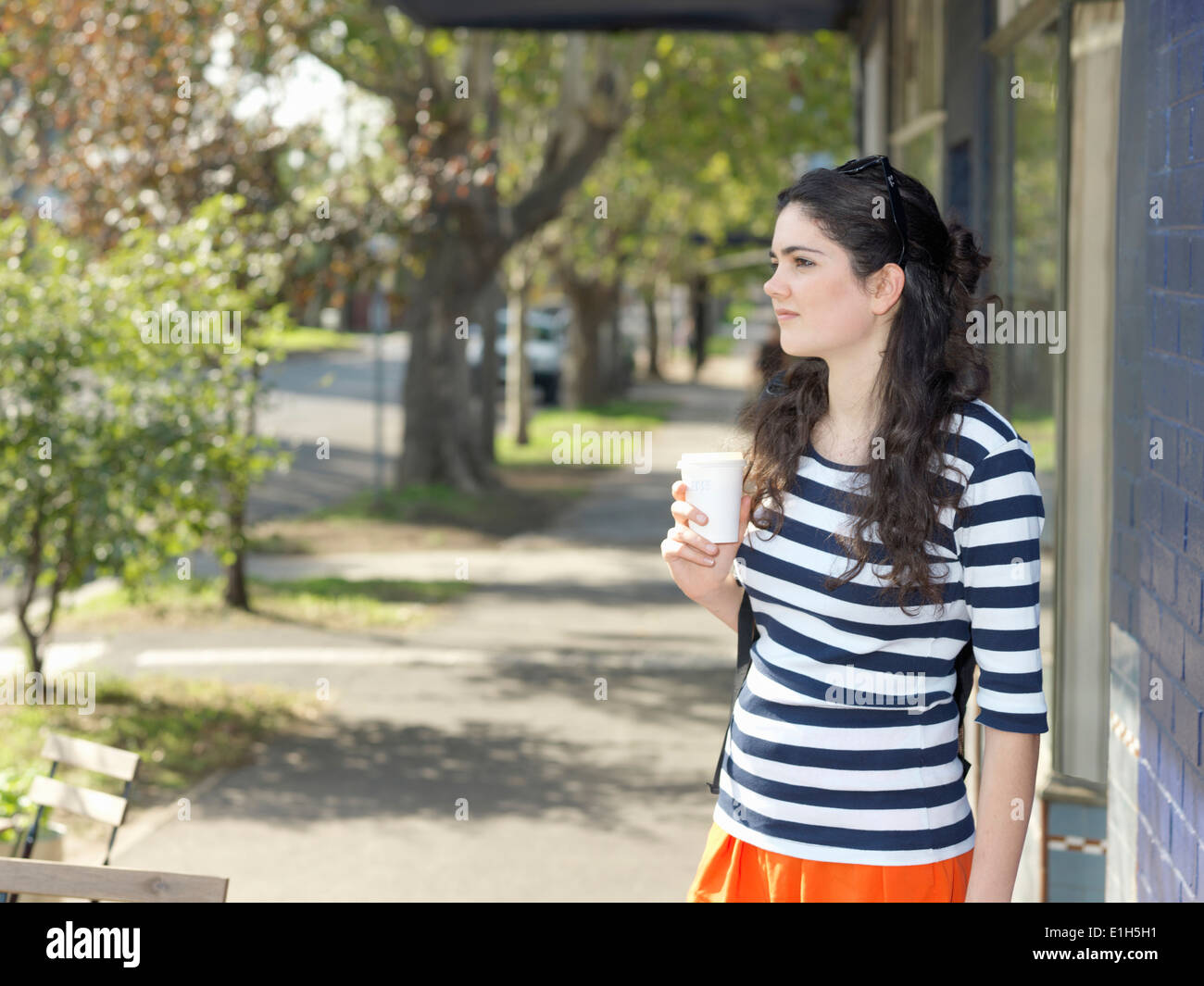 Young woman with takeaway coffee waiting on street - Stock Image