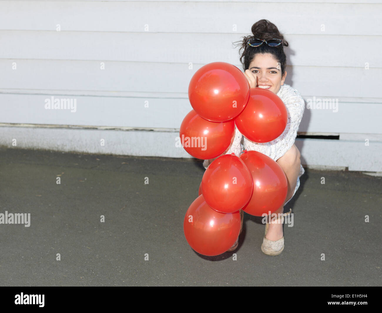 Portrait of young woman crouching with a bunch of balloons - Stock Image