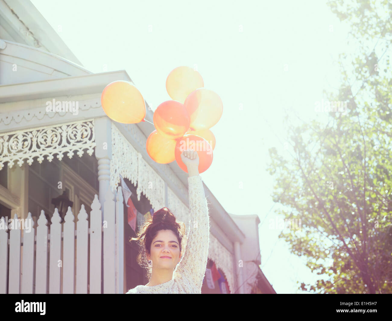 Portrait of young woman holding up a bunch of balloons - Stock Image