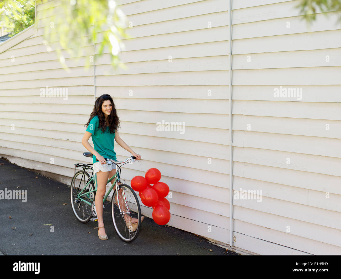 Portrait of young woman with bicycle and a bunch of balloons Stock Photo