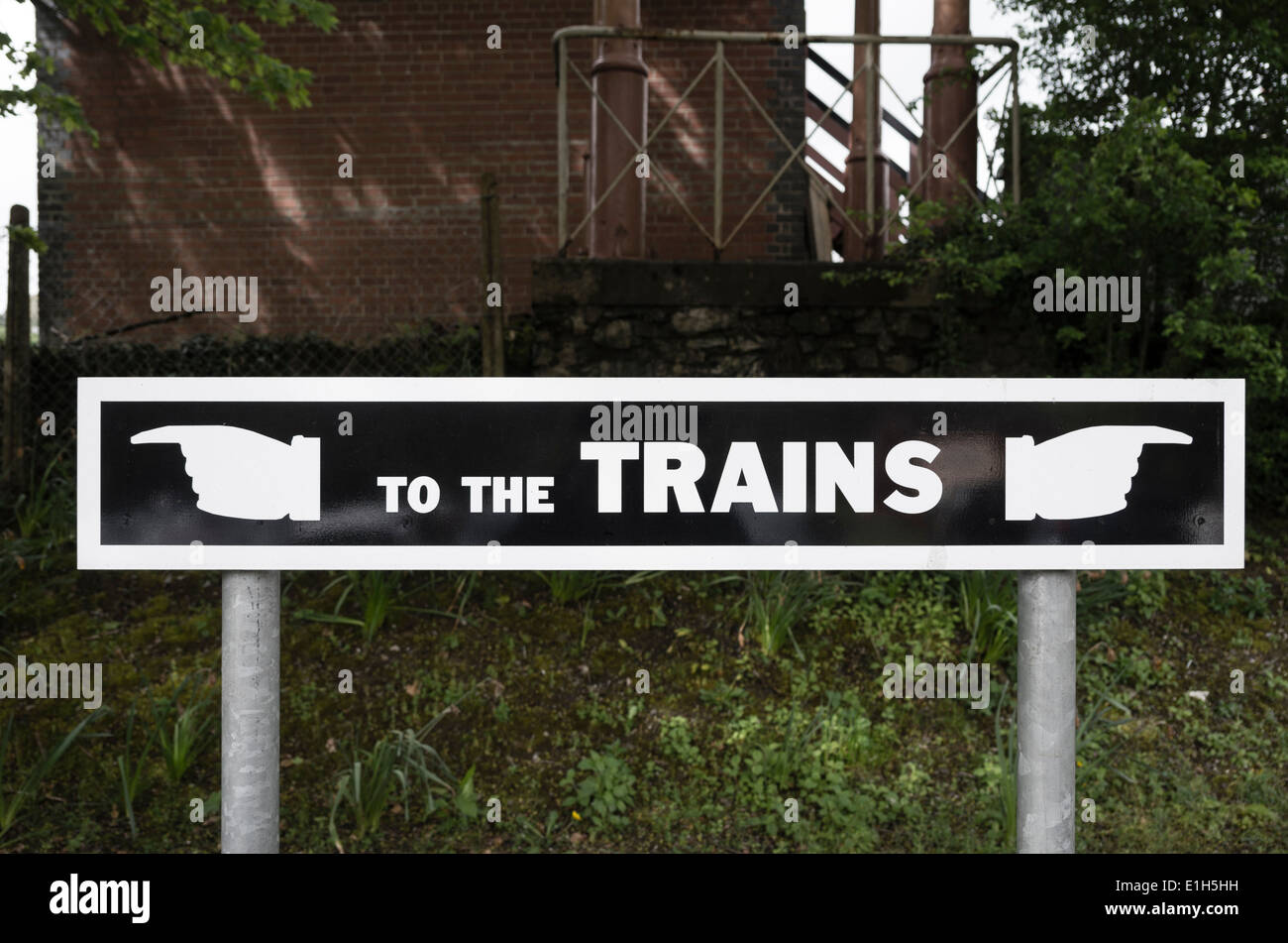 Ambiguous sign pointing two directions to the trains in UK - Stock Image