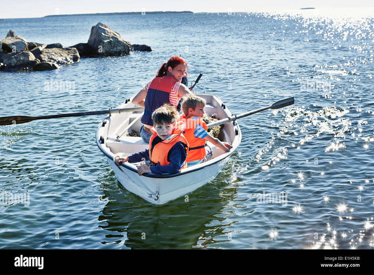 Mother and two young sons in rowing boat on lake, Gavle, Sweden - Stock Image